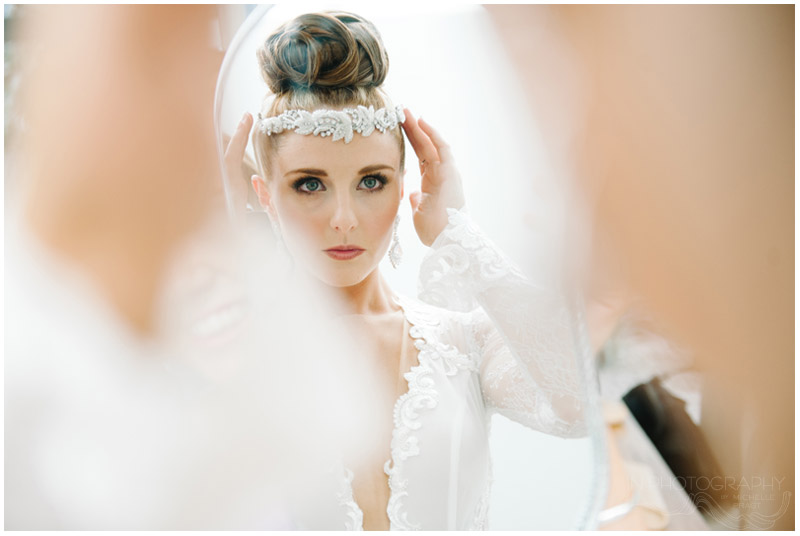 bride adjusts beaded hair piece