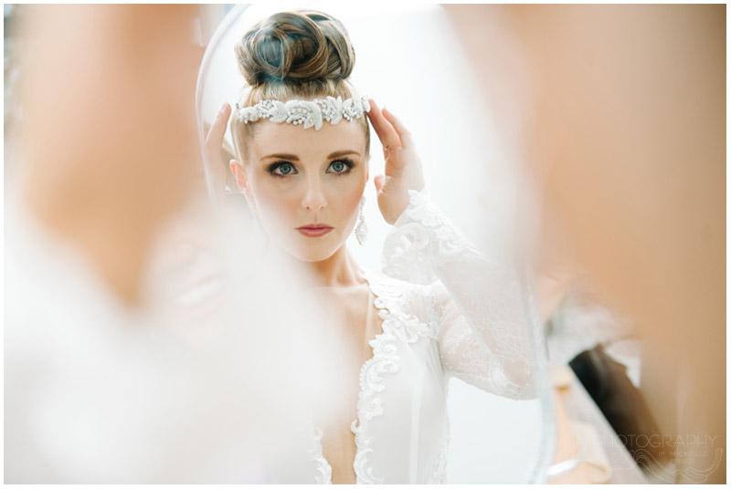 bride adjusts beaded hair piece